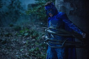 Mihajlo Milavic as Shade in a blue superhero outfit tied to a tree in the woods