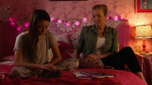 Kate Alberts and Wendi McLendon Covey sitting on a bed talking.