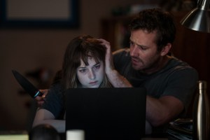 Dakota Johnson and Armie Hammer sit in front of a laptop. Armie is holding a knife and petting Dakota's hair