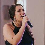 Amanda Lopez holding a microphone, singing