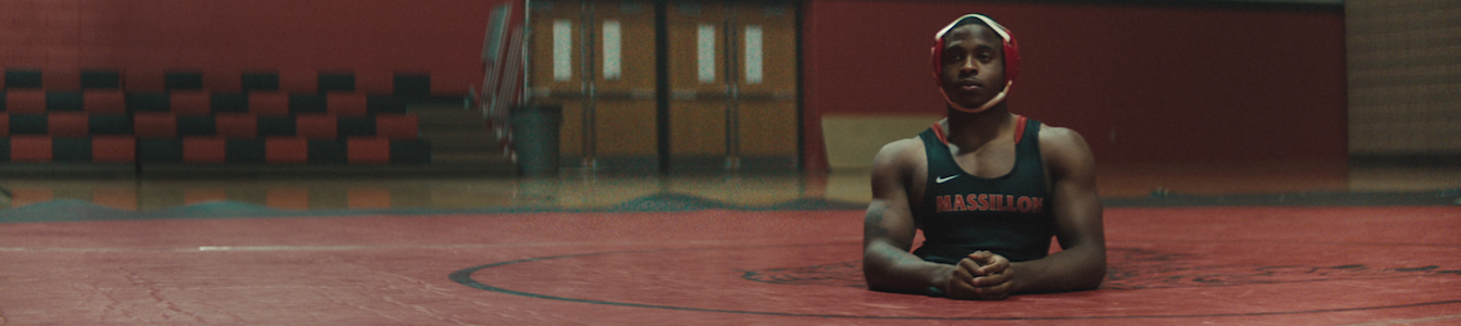 Zion in uniform on the mat in the gym