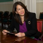 Carol Robles-Román sitting at a table holding an iPad, smiling looking to her left