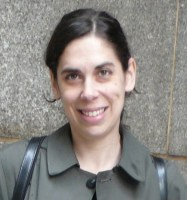 Dr. Jordana Mendelson smiling in front of a wall