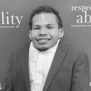 Justin Tapp smiling in front of the RespectAbility banner
