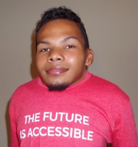 "Justin Tapp smiling wearing a pink t shirt that says ""The Future Is Accessible"""