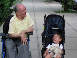 Guila Franklin Siegel's dad and her son laughing. Her dad is in a wheelchair and her son is in a stroller