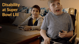 Still from Microsoft Commercial with two young boys playing video games, one of whom is a wheelchair user and playing with their adaptive controller. Text: Disability at Super Bowl LIII