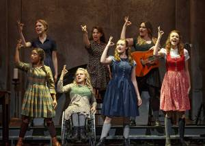 The cast of Spring Awakening with their right hands up on stage as part of a musical number