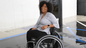 Tatiana Lee smiling in a parking lot. Tatiana is a wheelchair user.