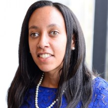 Haben Girma wearing a blue dress and pearls