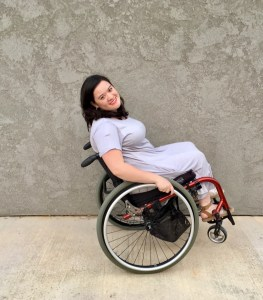 Cami Howe smiling, leaning back in her wheelchair
