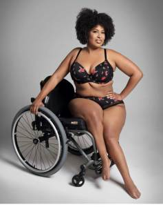 Tatiana Lee in lingerie holding onto her wheelchair behind her.