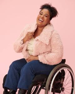 Tatiana Lee in a wheelchair wearing a pink jacket smiling