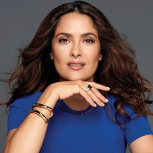 Salma Hayek wearing a blue top with her hand under her chin smiling for the camera