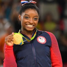 Simone Biles holding her gold medal at the Olympics