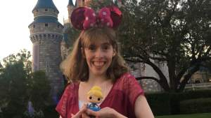 Emily Kranking with Minnie Mouse ears in front of Cinderella Castle holding a toy doll