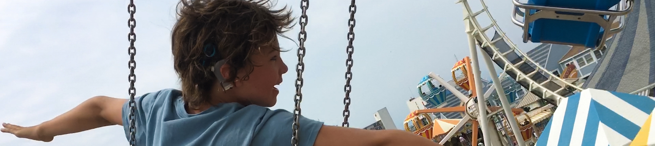 A still from Moonlight Sonata: Deafness in Three Movements with a young boy on an amusement park ride with his arms extended. Courtesy of Sundance Institute/photo by Irene Taylor Brodsky