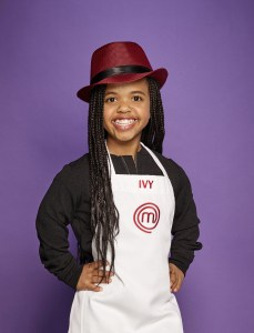 Ivy wearing her MasterChef Junior Jacket, smiling in front of a plain purple wall