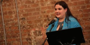 Rachel Kunstadt behind a microphone and a music stand and in front of a brick wall
