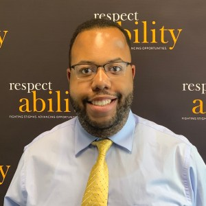 Anthony Brown smiling in front of the RespectAbility banner