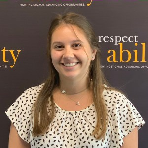 Elizabeth Batwinis, smiling in front of the RespectAbility banner
