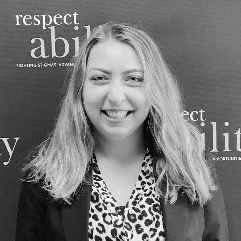 Sarah Meehan smiling in front of the RespectAbility banner