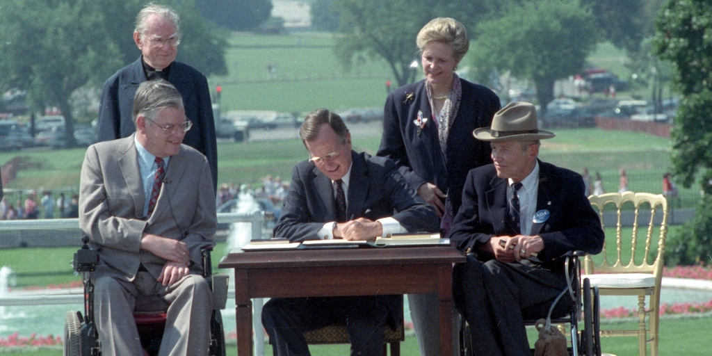 George H.W. Bush signs the ADA into law with four people around him, two of whom are wheelchair users