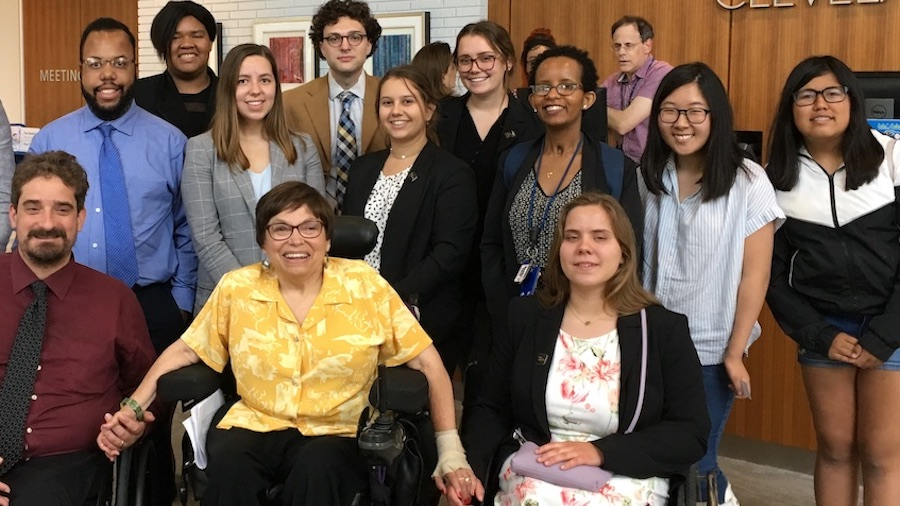 Judy Heumann with RespectAbility summer 2019 fellows inside the Cleveland park library, smiling