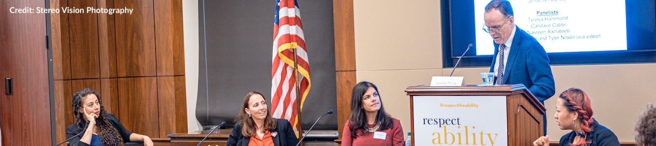 L-R: Nasreen Alkhateeb, Candace Cable, Teresa Hammond and Jonathan Murray. Jonathan is behind a podium while the three women are sitting behind a table in front of an American flag. Credit: Stereo Vision Photography