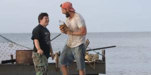 "Zak (Zack Gottsagen), left, and Tyler (Shia LaBeouf), right, near a raft they built in ""The Peanut Butter Falcon"""