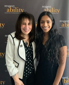 Vivian Bass and Shivani Gandhi smiling together in front of the RespectAbility banner