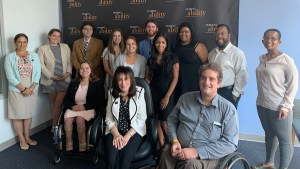Vivian Bass with RespectAbility Staff and Summer 2019 Fellows smiling in front of the RespectAbility banner