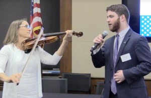 Adam Fishbein singing the national anthem in front of an American flag with Debbie Fink accompanying him on violin.