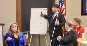 Ollie Cantos writing on a flip chart holding a walking stick, as Jennifer Laszlo Mizrahi and Steve Bartlett look on seated at a table. Sign language interpreter is in the lower left of the frame. American flag in the background