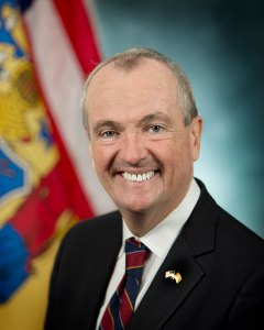 New Jersey Governor Phil Murphy smiling in front of the state flag.