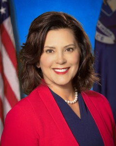 Governor Gretchen Whitmer smiling in front of an American flag and a Michigan state flag