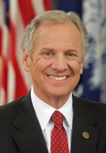 Governor Henry McMaster smiling in front of an American flag.