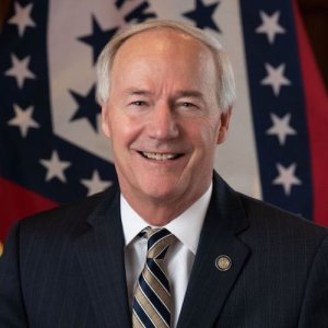 Arkansas Governor Asa Hutchinson smiling in front of the state flag.