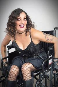 Filmmaker Diana Romero dressed in black, smiling. Romero is a wheelchair user
