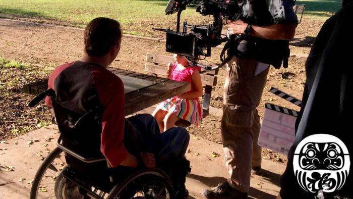 Tobias Forrest and a young girl on the set of Daruma with a camera pointed at Tobias. Logo for Daruma in bottom right.