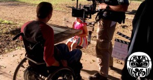 Tobias Forest and a young girl on the set of Daruma with a camera pointed at Tobias. Logo for Daruma in bottom right.