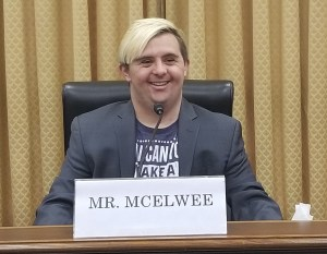 Sean McElwee sits in a hearing room behind a sign that says Mr. McElwee