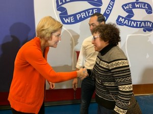 Elizabeth Warren shakes hands with Ila Eckhoff as Julian Castro looks on.