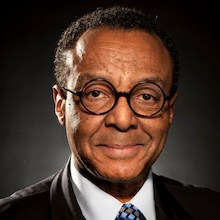 Clarence Page headshot wearing black suit, white shirt and glasses