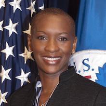 Claudia Gordon smiling in front of an American flag