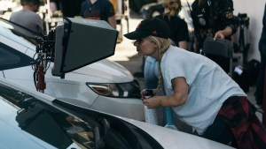 Ashley Eakin on the set of a film shoot looking into a monitor next to two cars