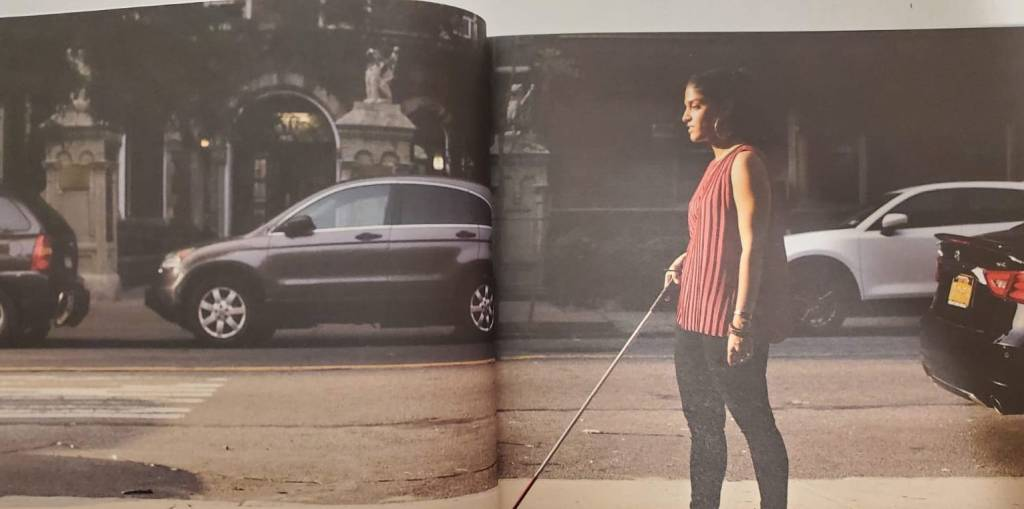 Magazine spread of Khadija Bari walking down a street holding a white cane