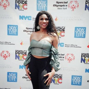 Lachi on a red carpet in front of logos for Disability Pride NYC, the Christopher and Dan Reeve Foundation, Special Olympics New York, and New York Life