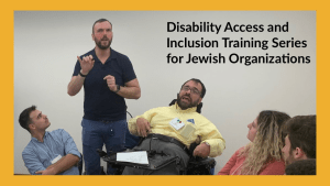 A man using a wheelchair next to an ASL interpreter speaks as three other people look on seated. Text: Disability Access and Inclusion Training Series for Jewish Organizations