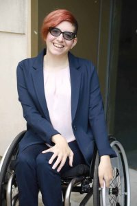 Lauren Arena smiling wearing glasses and a suit jacket. Arena is a wheelchair user.